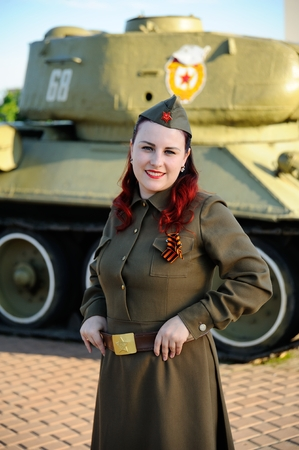 A girl in the military uniform of a Soviet soldier against the backdrop of a tank. Victory Day, May 9, against fascism