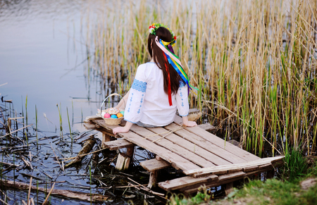 revive: beautiful girl in Ukrainian national clothes in a wreath of flowers on her head with the Easter basket on the background of the river Stock Photo