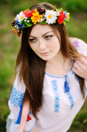slavs: beautiful young girl in a wreath from flowers on head on the background of nature in spring