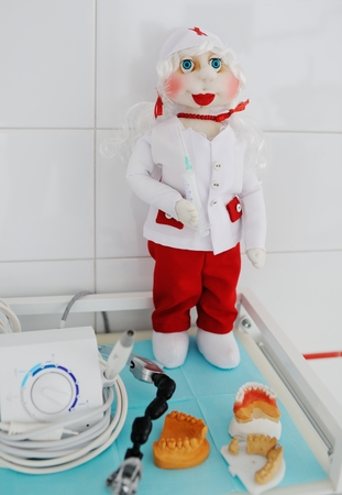 Doll dentist on a background of dentures close-up