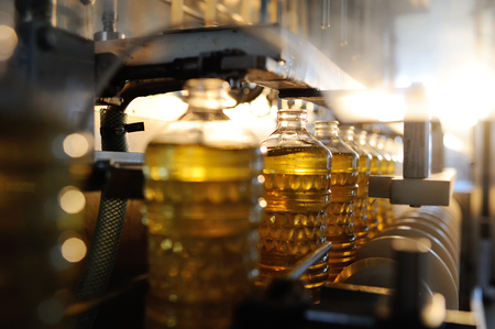 Sunflower oil. Line for the production and bottling of refined oil from sunflower seeds. Conveyor of food industry Standard-Bild