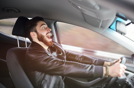 A young man scared screaming at the wheel of the car before the accident. Road traffic accident, collision on the road.