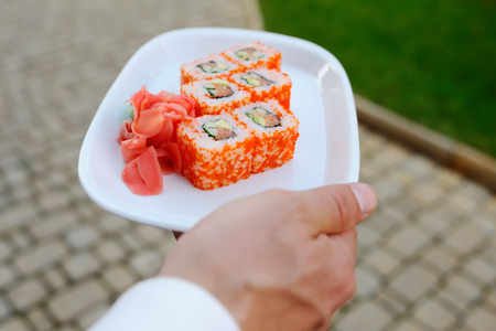 waiter carries a platter of California rolls. delivery rolls