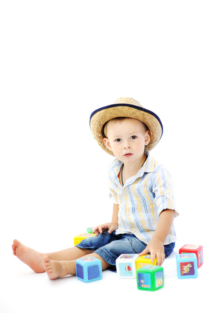 barefoot cowboy: baby boy in a straw hat playing with multicolored cubes on a white background Stock Photo