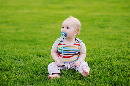 barefooted baby with a pacifier is sitting in the grass Stock Photo