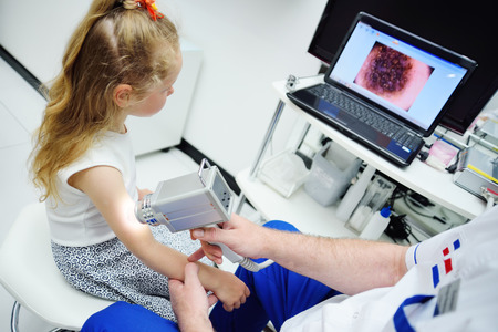 피부과 전문의는 dematoscopy - dermatoscope에 대한 특별한 장치의 도움으로 환자의 두더기를 검사합니다. 흑색 종의 예방 스톡 콘텐츠