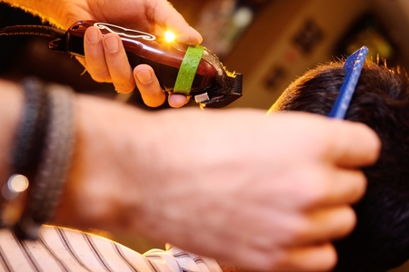 barber: hairdresser or barber does a hairstyle to the client on the background of modern barbershop Stock Photo