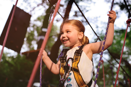 cute baby girl in climbing gear on a rope park background