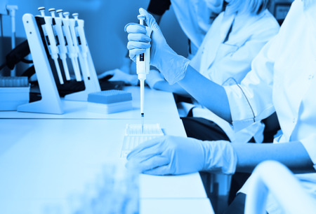A scientist in a medical laboratory with a dispenser in his hands is doing an analysis