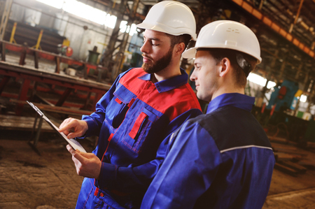 Engineer-constructor and worker discuss the construction project against the background of an industrial plant