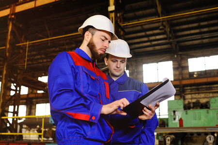 Two industrial workers in construction helmets discuss the project Stok Fotoğraf