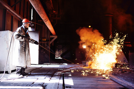 A man working at a metallurgical plant against a blast furnace, molten metal, and sparks Stock Photo