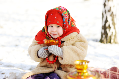 little girl in a fur coat and red scarf Russian drinking tea on a background of a samovar. Portrait of girl dressed in Russian style on a background of a samovar