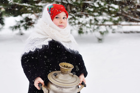 child girl in a fur coat and headscarf in Russian style holding a large samovar on the background of snow and forest. Maslenitsa, Russia, tea drinking, traditional, carnival