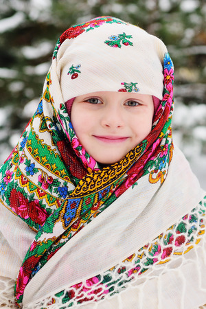 portrait of a child girl in a headscarf in the Urs style on the background of snow and forest. Russia, frost, fairy tale, carnival