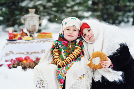 two little girls in fur coats and shawls in Russian style on the background of pancakes with red caviar, bagels, samovar, Russian dolls and winter wood. Celebration of the carnival. Russia, Shrovetide.
