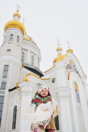 A little girl in a fur coat and a Russian scarf on the background of an Orthodox church. Christmas, Epiphany, Russia, Pancake week.