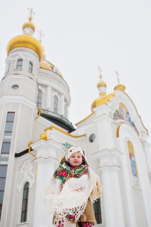Une petite fille dans un manteau de fourrure et une écharpe russe sur le fond d'une église orthodoxe. Noël, Épiphanie, Russie, Semaine des crêpes. Banque d'images