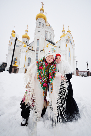 Two little girls in fur coats and shawls in Russian style against the background of a Christian church. Christmas, christening, winter, Russia, snow, religion