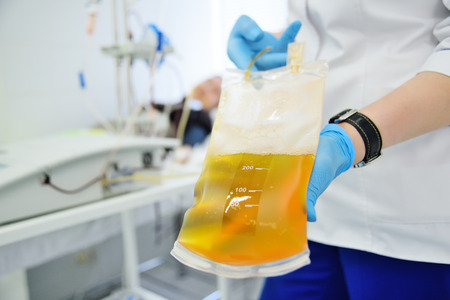 看護婦の手の中のビニール袋の中のプラズマ 写真素材