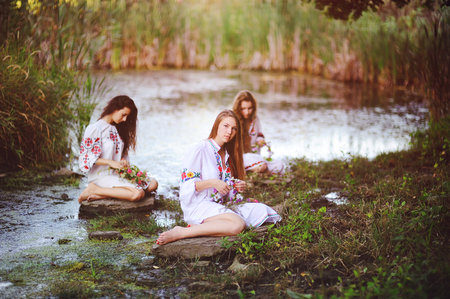 three young beautiful girls in white shirts with floral ornaments with wreaths in their hands sitting on the background of the river. Midsummer Day, Midsummer, divination, Ukrainian, Slavic, pagan.