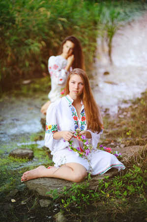 two young beautiful girls in white shirt with floral ornament with wreaths in their hands sitting on the background of the river. The celebration of the pagan Slavic holiday of Ivan Kupala Day or Midsummer.
