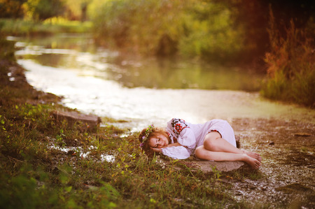 cute young girl in white shirt with floral ornament and wreath of flowers on her head sleeping on the background of the river and beautiful nature. Pagan Slavic holiday Ivan Kupala Day or Midsummer day. Stock Photo