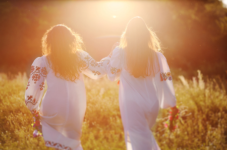 two young beautiful girls in white shirts with floral ornament with flower wreaths in their hands run against the background of nature and grass in the contour or the back light of the sun. The celebration of the Slavic pagan holiday of Ivan Kupala Day or Midsummer.