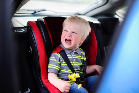 cute baby boy blondes crying in a childrens car seat 版權商用圖片