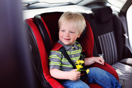 portrait of a young child of a boy with blond hair in a childrens car seat. Safe transportation of children in the car.