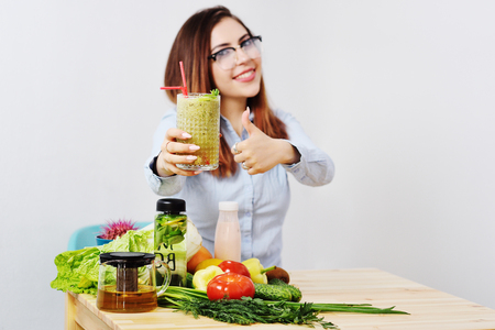 cute young girl in glasses with a glass of smoothies in hands. Healthy Eating, Weight Loss, Vegetarianism