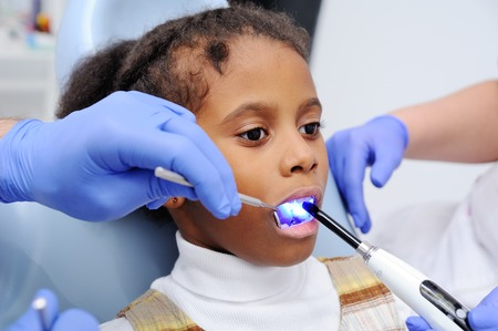 a dark-skinned baby girl in the dentists chair.dentist shines a UV lamp at the little patients teeth.