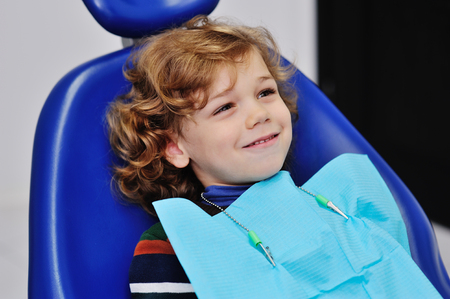 cheerful child boy with curly red hair in blue dental chair smiling Stock Photo