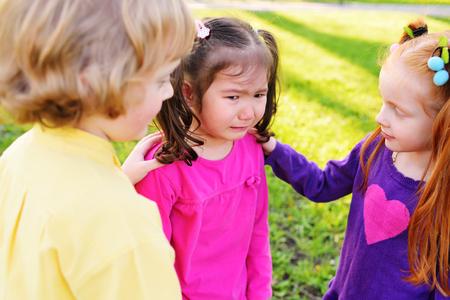 i bambini si sentono dispiaciuti per una bambina che piange. Infanzia, amici, pianto, amicizia, pietà, sentimenti di compassione Archivio Fotografico