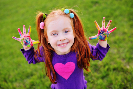 cheerful little girl with red hair shows her hands dirty with multicolored paints and smiles