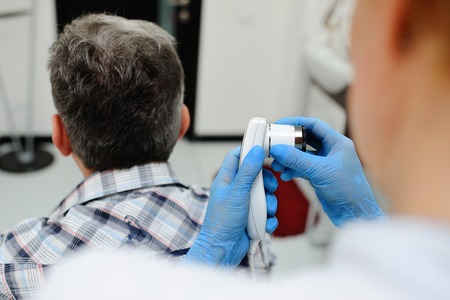 a man with gray hair at the reception at the dermatologist. the doctor examines the patients hair using a method trihoskopii