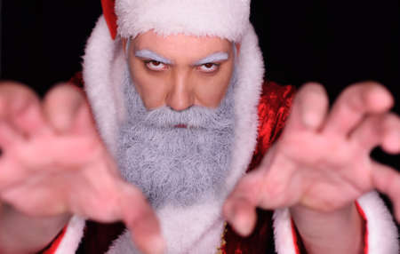 evil Santa Claus  angrily looks at the camera on a dark background