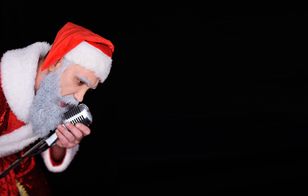 santa claus with a microphone sings a song in karaoke.Copy space