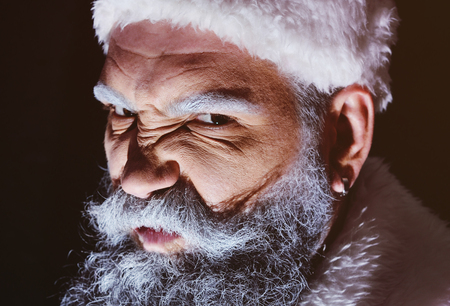Angry Santa furiously grimaces against a dark background Standard-Bild - 109609040