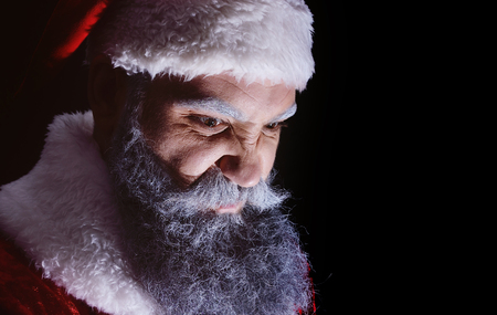 evil Santa Claus grimaces and scares a terrible face on a dark background