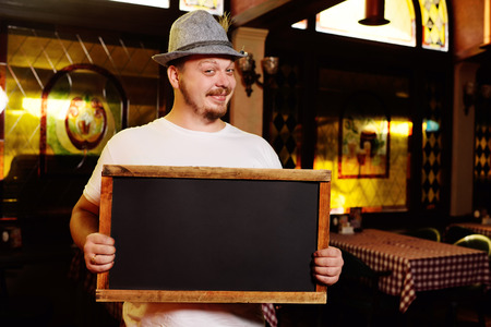 a fat cheerful man in a Bavarian hat with a feather during the celebration of Oktoberfest holds a sign or chalkboard in his hands. Place for tex, copy space Stock Photo