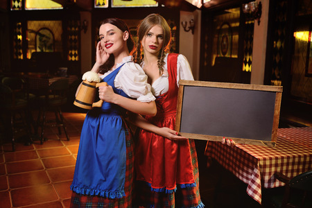 two young attractive girls in traditional Bavarian clothes with chalk Board and a glass of beer in their hands on the background of the pub during the Oktoberfest celebration. Standard-Bild - 110222684