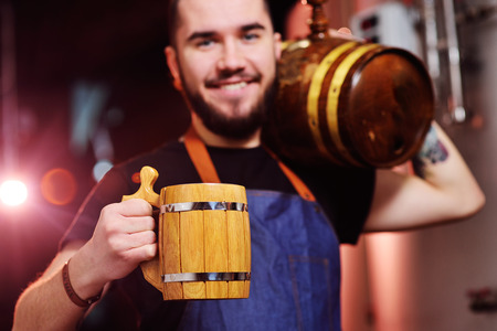young attractive bearded brewer with a wooden mug in his hands and with a barrel of beer smiling at the background of the brewery Standard-Bild - 109609951