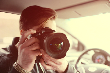 A photographer with a camera in the car is preparing to make an important shot. Spy, paparazzi, journalist. Standard-Bild - 109609953
