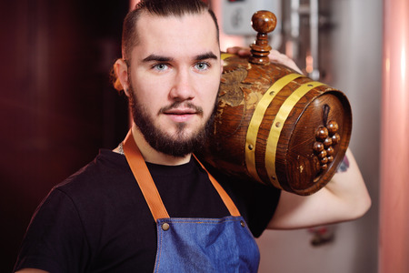 a young attractive winemaker holds a wooden barrel of wine Standard-Bild - 109609955
