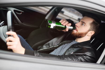 A young handsome bearded man with a bottle of beer or a low-alcohol drink at the wheel of a car. Driving in a state of intoxication Standard-Bild - 109609959