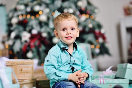 baby boy opens boxes with gifts under the Christmas tree and smiles Standard-Bild - 109609962