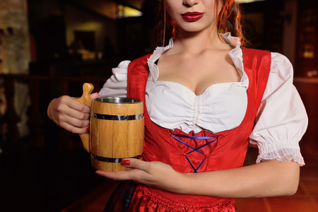 attractive young girl in traditional Bavarian clothes with a wooden mug of beer on the background of the pub during the celebration of Oktoberfest Standard-Bild - 109610031