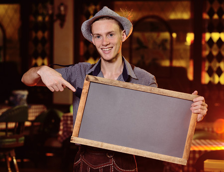 a young attractive male waiter in Bavarian clothes and wearing a hat with a feather holding a chalkboard or a plaque in his hands. Copy space Standard-Bild - 109610033