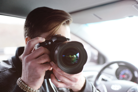 A photographer with a camera in the car is preparing to make an important shot. Spy, paparazzi, journalist. Standard-Bild - 109610039